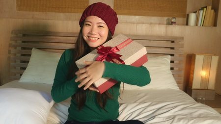 young happy and beautiful Asian American girl in winter hat holding Christmas giftbox with ribbon smiling excited and cheerful receiving x-mas present sitting at home bed opening box