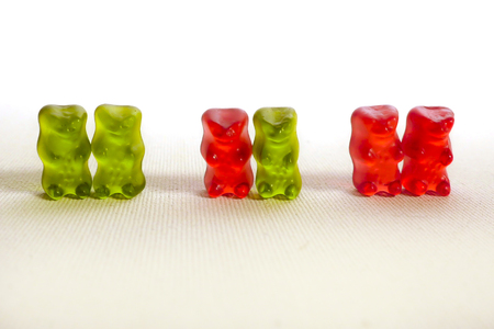 conceptual image of sweet candy gummy bears representing diversity of love with a men couple another heterosexual and lesbian women couple in gay marriage and homosexual people rights Stok Fotoğraf