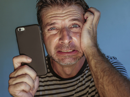 close up face portrait of young scared and stressed man using mobile phone looking confused feeling worried and frustrated in internet social media problem isolated on grey background