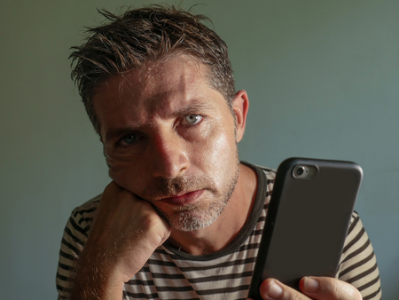 close up face portrait of young attractive and stressed man using mobile phone feeling worried and frustrated in internet social media problem isolated on grey background Imagens