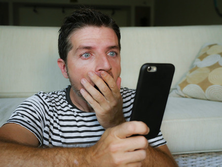 young perplexed and shocked man using mobile phone looking internet social media or checking news in surprised and crazy disbelief face expression feeling petrified and anxious Stock Photo