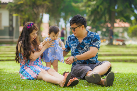 young happy and loving Asian Japanese family with parents and sweet baby daughter at city park together with father taking selfie pic with mobile phone for uploading on internet social media