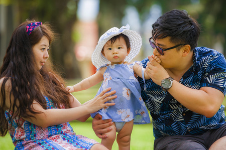 young happy and loving Asian Korean parents couple enjoying together with sweet daughter baby girl sitting on grass at green city park in healthy beautiful parenthood and childhood concept