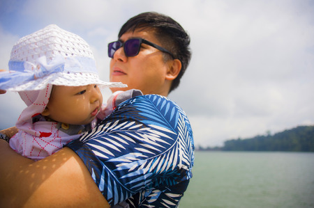 outdoors lifestyle portrait of young happy and proud Asian Chinese man as loving father holding adorable daughter baby girl during holidays excursion in family travel and tourism concept
