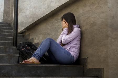 giovane studentessa triste e depressa o ragazza adolescente vittima di bullismo seduta all'aperto sulla scalinata della strada vittima spaventata e ansiosa del bullismo sensazione disperata sofferenza problema di depressione