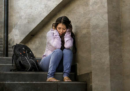 young sad and depressed Asian Japanese student woman or bullied teenager sitting outdoors on street staircase overwhelmed and anxious feeling desperate suffering depression problem