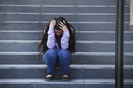 young sad and depressed Asian American student woman or bullied teenager sitting outdoors on street staircase overwhelmed and anxious feeling desperate suffering depression problem Banque d'images
