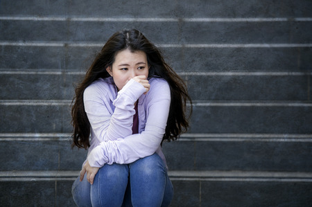 young sad and depressed Asian Chinese student woman or bullied teenager sitting outdoors on street staircase overwhelmed and anxious feeling desperate suffering depression problem Stock Photo