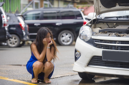 young desperate and worried Asian Korean woman in stress stranded on roadside with car engine failure having mechanic problem needing repair service squating on street feeling upset