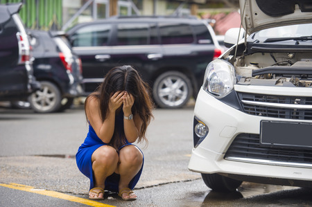 young desperate and worried woman in stress stranded on roadside with car engine failure having mechanic problem needing repair service and assistance squating on street upset and overwhelmed