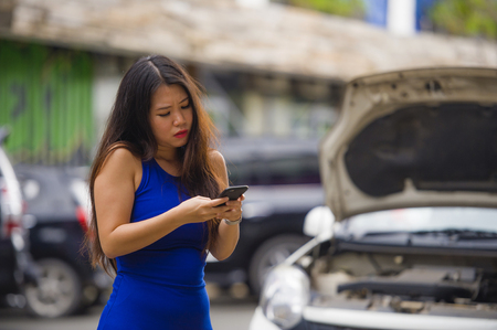 young desperate and upset Asian Chinese woman in stress stranded on street suffering car engine failure having mechanic problem calling on mobile phone for help to insurance assistance service