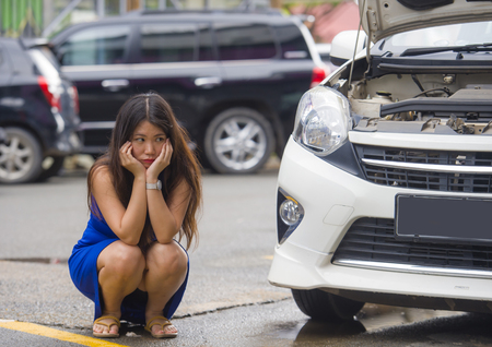 young desperate and worried Asian Chinese woman in stress stranded on roadside with car engine failure having mechanic problem needing repair service squating on street feeling upset