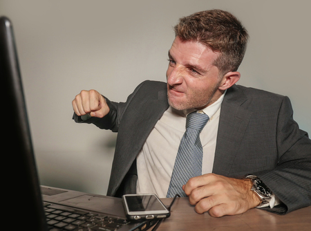 young stressed and overwhelmed businessman in suit and tie working angry at office laptop computer desk looking furious and upset in financial business stress problem at corporate job