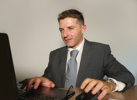 young attractive and happy businessman in suit and necktie working on office laptop computer desk isolated on even background smiling successful and confident in corporate job lifestyle