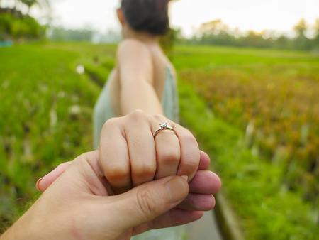 Nahaufnahme Paar Hände Mann, der glückliche Verlobte Hand mit Diamant-Verlobungsring am Finger hält, nach dem Heiratsantrag an einem tropischen schönen und romantischen Ort, der die Ehe vorschlägt