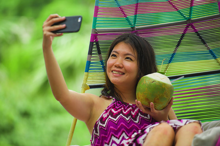 young beautiful and happy Asian Chinese tourist woman drinking coconut water taking selfie picture with mobile phone at luxury tropical island resort swimming pool enjoying summer holidays Imagens