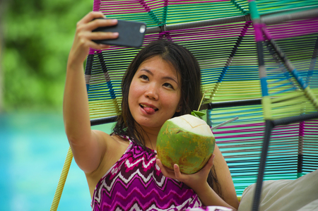 young beautiful and happy Asian Korean tourist woman drinking coconut water taking selfie picture with mobile phone at luxury tropical island resort swimming pool enjoying summer holidays