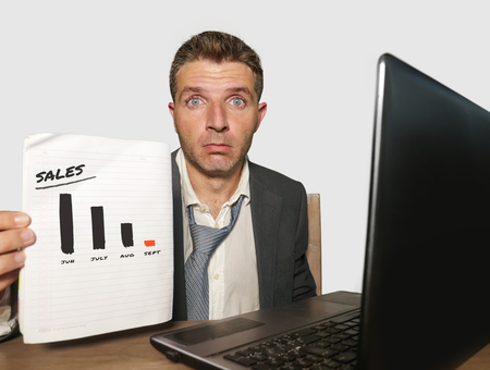 young depressed businessman working in stress at office computer desk holding notepad showing massive benefits loss and sales drop graph in corporate job problem and business crisis