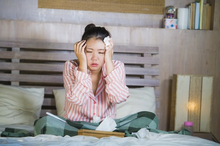 young beautiful and sweet Asian Korean girl in pajamas sick at home bedroom suffering cold and flu taking temperature with thermometer in bed blowing her nose coughing and sneezing Stock Photo