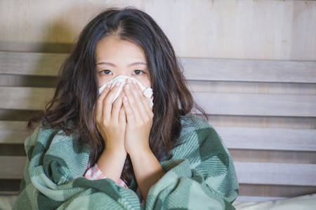 young beautiful and sweet Asian Korean girl in pajamas covered with blanket sick suffering cold and flu taking temperature with thermometer in bed feeling feverish blowing her nose coughing