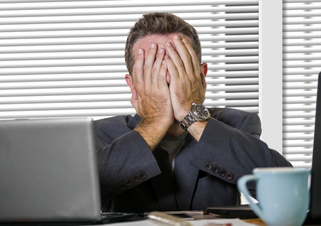 young attractive upset and stressed businessman working overwhelmed suffering stress at office computer desk in corporate business job problem covering his face worried and depressed