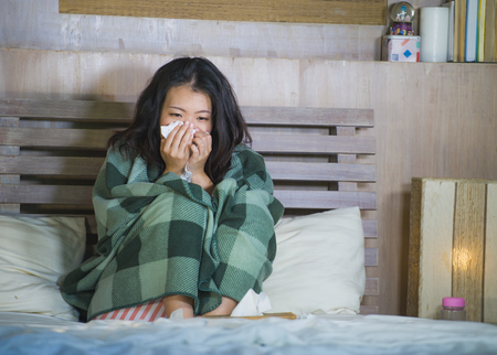 young beautiful and sweet Asian Korean woman in pajamas covered with blanket sick suffering cold and flu taking temperature with thermometer in bed feeling feverish blowing her nose coughing