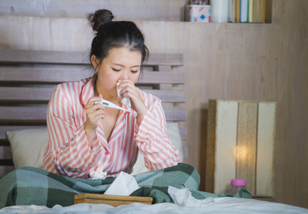 young beautiful and sweet Asian Japanese girl in pajamas sick at home bedroom suffering cold and flu taking temperature with thermometer in bed blowing her nose coughing and sneezing Stock Photo