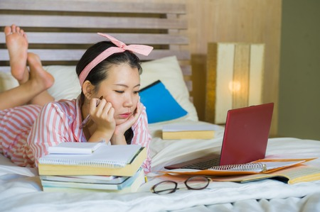 young confident and beautiful Asian Chinese student girl preparing University exam studying at home bedroom with laptop computer relaxed on bed in education and academic success concept Stockfoto