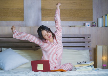 young beautiful tired and sleepy Asian Japanese student girl stretching in bed after long hours studying late for college exam with laptop computer in education success and academic lifestyle 스톡 콘텐츠