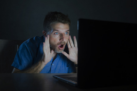 isolated portrait of young surprised and shocked man at night working with laptop computer in the dark in disbelief and surprise face expression watching something unbelievable in the internet