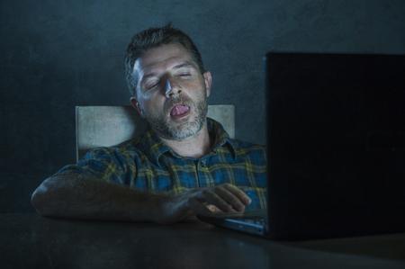 Joven adicto excitado y emocionado viendo el móvil en línea en la noche de la luz de la computadora portátil en el escritorio de la casa en concepto de adicción y contenido de Internet Foto de archivo