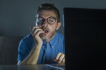 Joven adicto lascivo y excitado con gafas nerd viendo películas en línea a altas horas de la noche en la computadora portátil mirando pervertido y en Internet y contenido