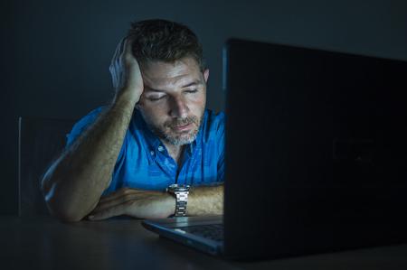 jeune homme non rasé attrayant et fatigué travaillant tard dans la nuit sur un ordinateur portable dans le noir se sentant frustré et épuisé par le concept d'entreprise d'entrepreneur indépendant
