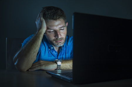 young attractive and tired unshaven man working late night on laptop computer in the dark feeling frustrated and exhausted in freelance entrepreneur business concept