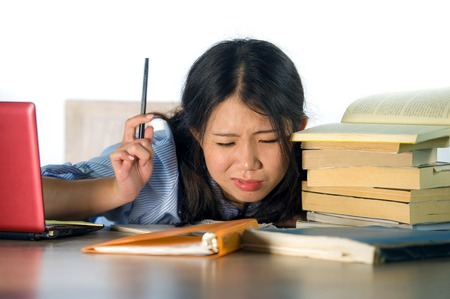 young stressed and frustrated Asian Chinese teenager student working hard with laptop computer and books pile on desk overwhelmed and exhausted feeling tired and worried isolated on white