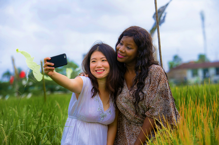 mixed ethnicity Asian Chinese girl and black Afro American woman taking girlfriends selfie with mobile phone together isolated at rice field enjoying exotic tropical holidays in traditional village