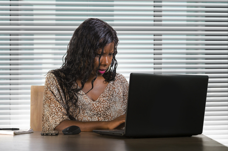 portrait of young beautiful and busy black afro American business woman working at office laptop computer desk by Venetian blinds window in corporate company job lifestyle