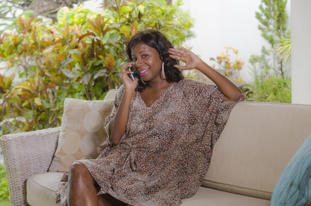 young beautiful and happy black African American woman talking on mobile phone cheerful and relaxed sitting at sofa couch in hotel resort or luxury villa garden in communication concept