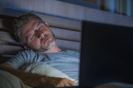 young tired and exhausted internet or work addict man sleeping while networking late night with laptop computer on bed in overwork and social media addiction concept