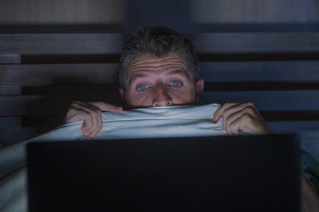 Lifestyle-Porträt eines jungen verängstigten und gestressten Mannes im Bett, der spät in der Nacht einen Internet-Horrorfilm mit Laptop-Computer oder Schlafzimmerfernsehen in panischem Gesichtsausdruck mit Decke ansieht