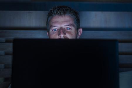 giovane attraente e rilassato internet addict uomo networking concentrato a tarda notte sul letto con computer portatile nella dipendenza dai social media o concetto di uomo d'affari maniaco del lavoro