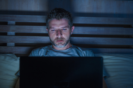 young attractive and relaxed internet addict man networking concentrated late at night on bed with laptop computer in social media addiction or workaholic businessman concept