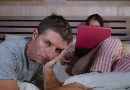 angry and frustrated husband moody in bed ignored by his workaholic wife or internet social media addict girlfriend using laptop in bed ignoring the man in couple problem and internet conflict 版權商用圖片