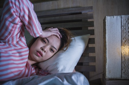 young beautiful sad and depressed Asian Chinese girl lying on bed late night awake looking thoughtful suffering insomnia sleeping disorder feeling tired and worried in woman depression concept Imagens