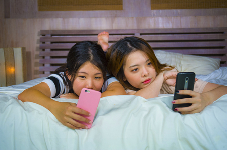 two young happy and pretty Asian Korean girlfriends sitting at home bedroom laughing and talking having fun using internet social media app with mobile phone sitting on bed in women friendship