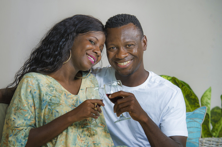 lifestyle home portrait of young romantic and happy black Afro American couple in love drinking wine cup at living room couch enjoying anniversary or Valentine sharing beautiful relationship Stock Photo