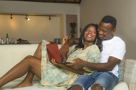 lifestyle home portrait of young happy and beautiful black African American couple in love enjoying at living room sofa couch with laptop computer having fun with internet  networking together 免版税图像