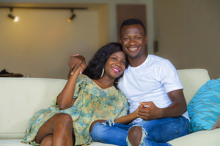 lifestyle home portrait of young happy and successful romantic afro American couple in love relaxed sitting comfortable together at living room sofa couch cuddling and smiling cheerful