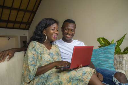 lifestyle home portrait of young happy and beautiful black African American couple in love enjoying at living room sofa couch with laptop computer having fun laughing relaxed networking together 免版税图像