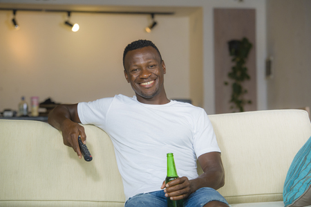 lifestyle candid portrait of young attractive and happy black afro American man holding TV remote controller watching television movie laughing relaxed drinking beer in living room couch at home
